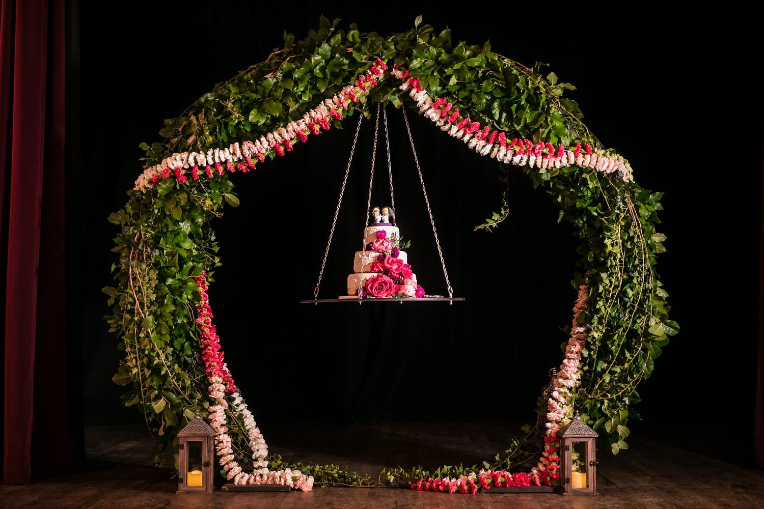 Three-tier pink floral wedding cake hanging from a swing | PartySlate