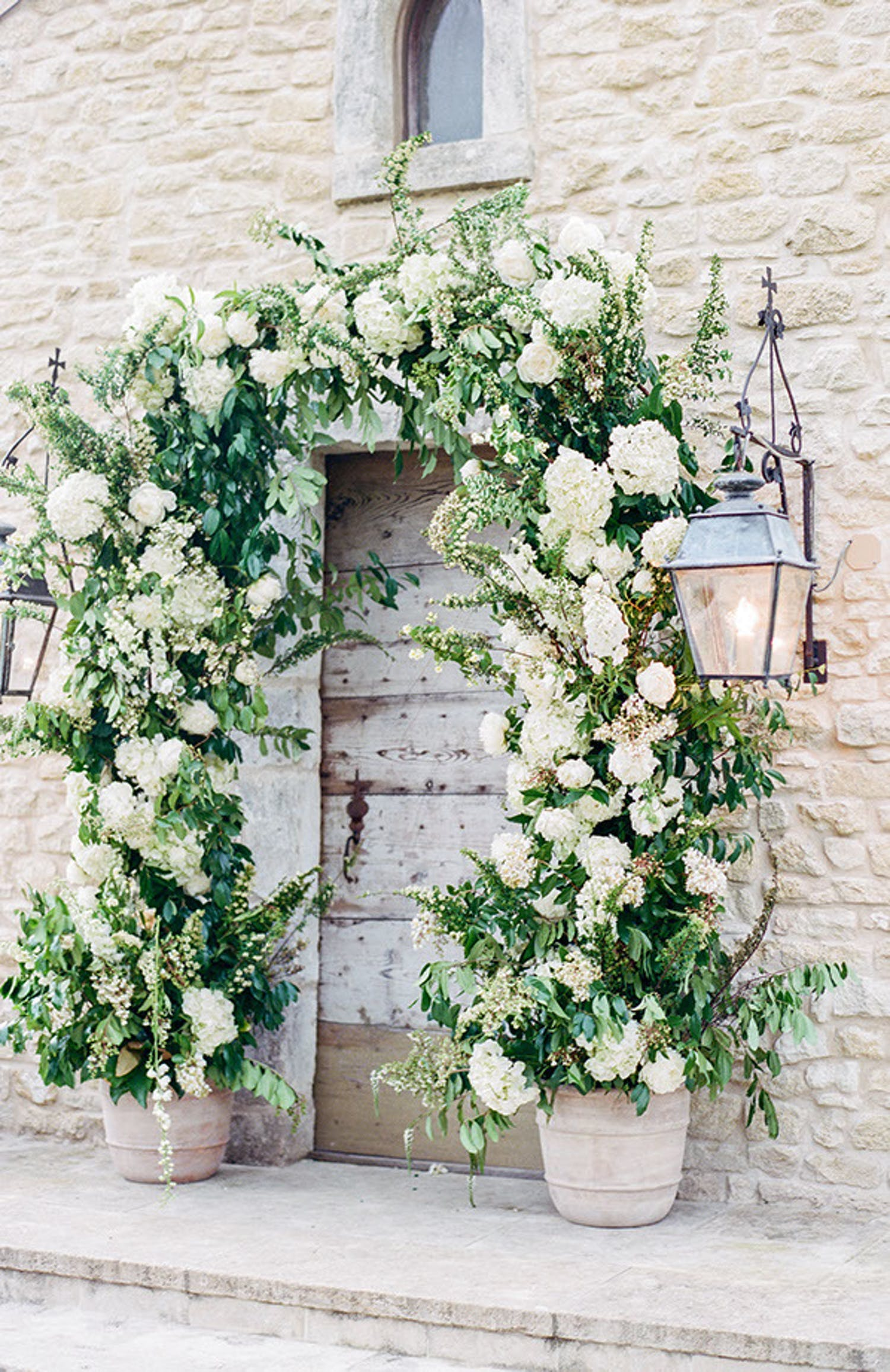 White and green floral arch over outside door at white country wedding designed by Events in Bloom   PartySlate