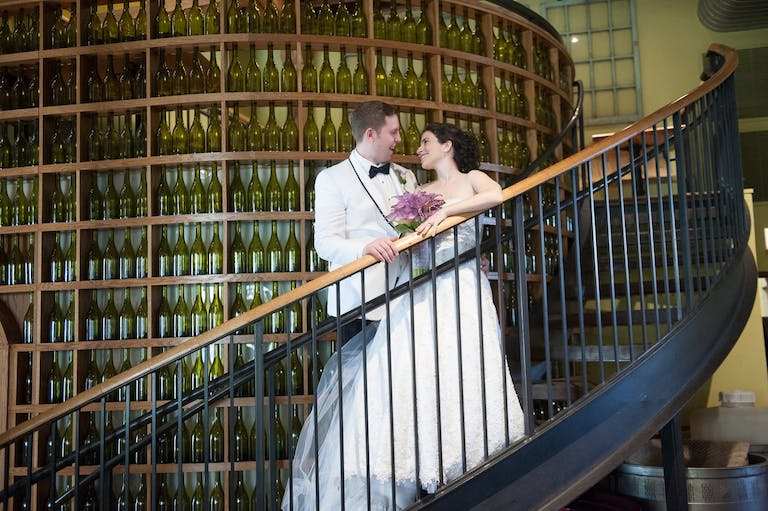 Bride and groom smile at each other on stairway curving around towering wine wall at City Winery Chicago in Chicago, IL   PartySlate