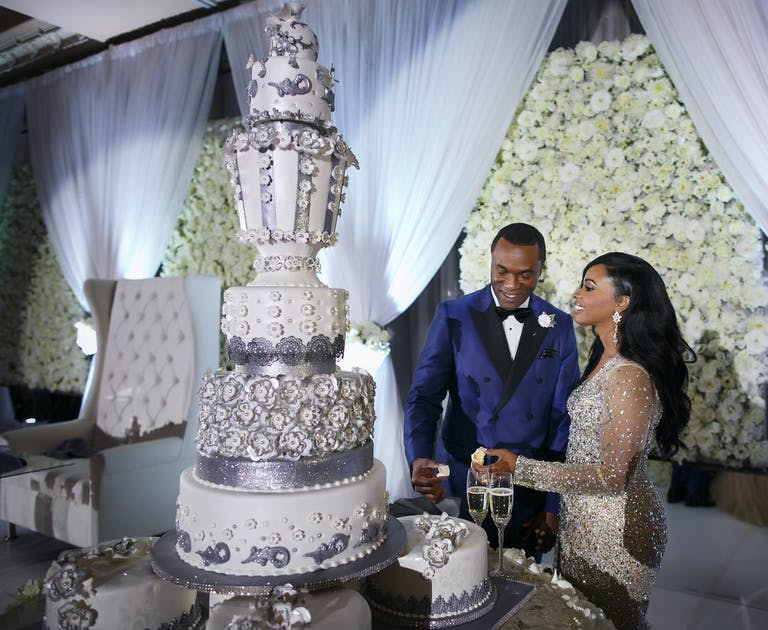 Bride and groom cut into towering white and silver luxury wedding cake designed by Edet Okon of Houston, TX   PartySlate