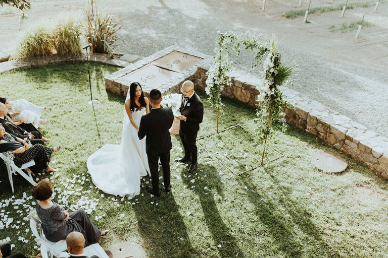 Bride and groom exchange vows at the end of a white petal blanketed aisle at Foley Sonoma, a California winery venue   PartySlate