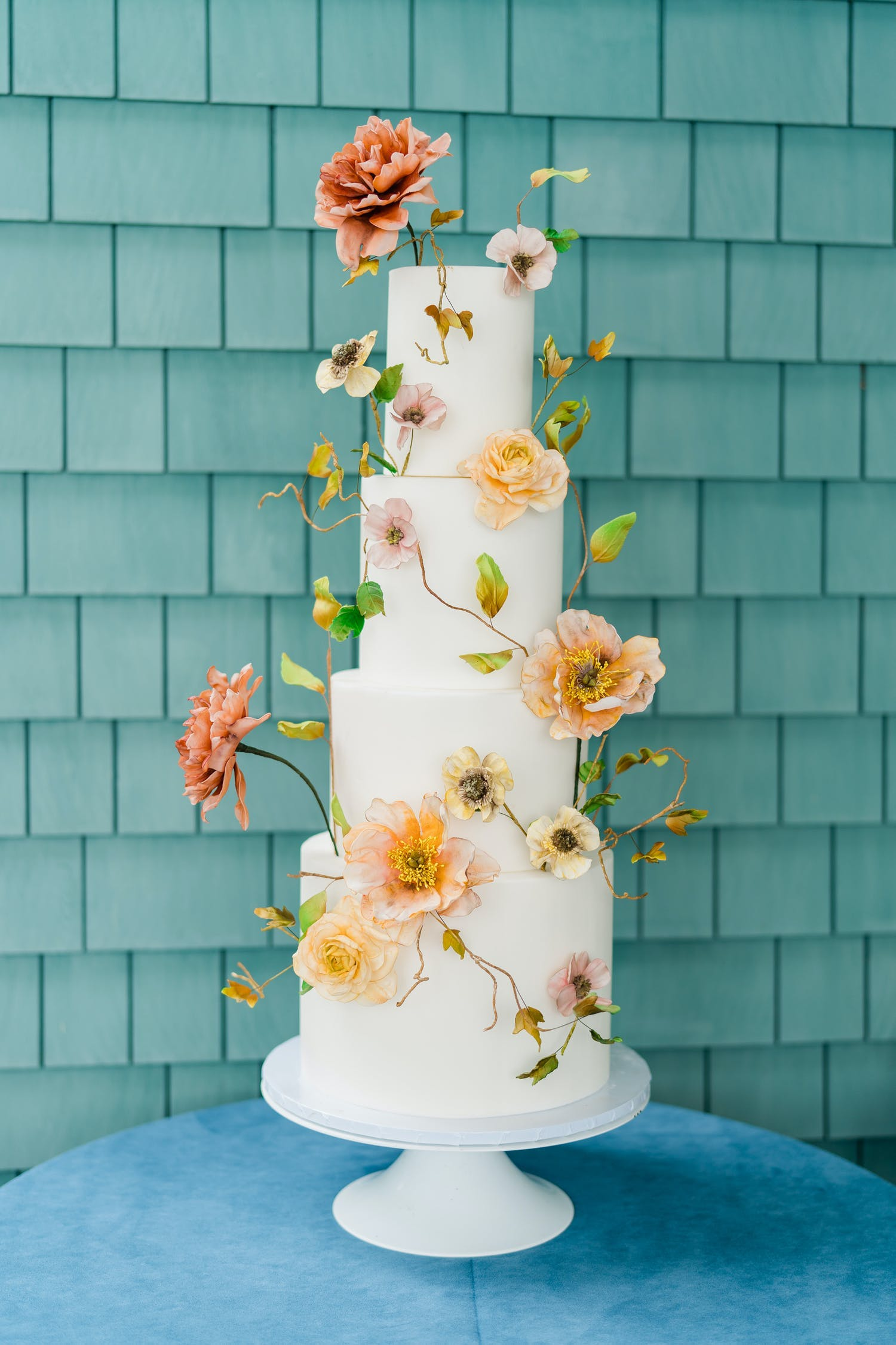 Simple and four-tier white wedding cake decorated with both flowers and stems | PartySlate