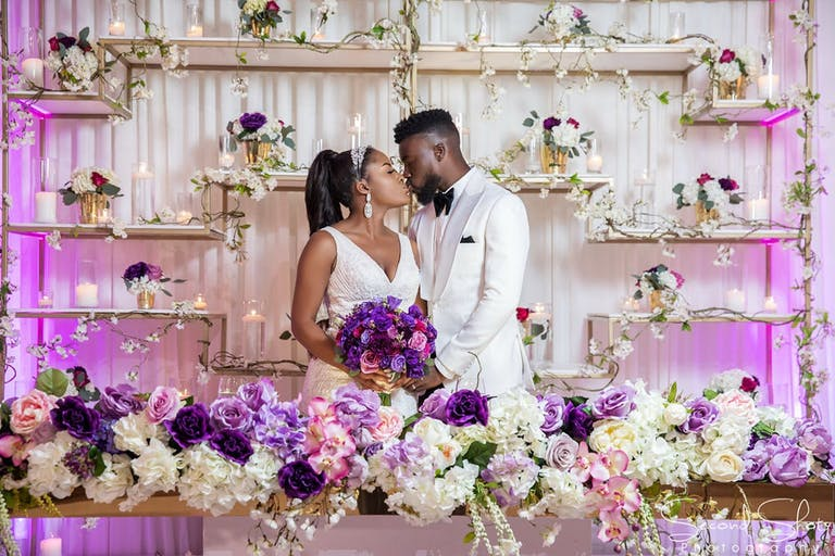 Bride and groom kiss in front of glamorous purple and gold wedding backdrop   PartySlate