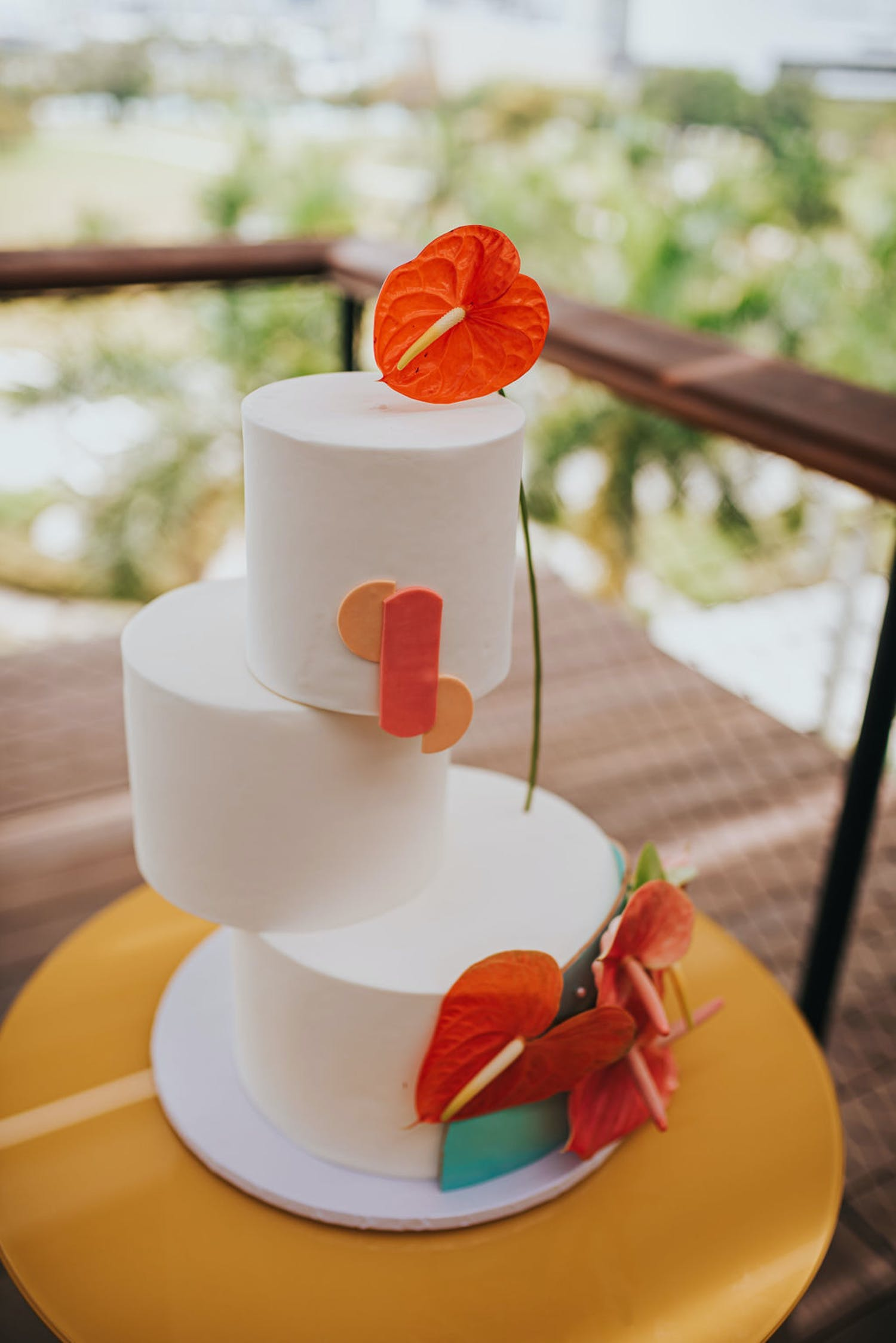 White three-tier circle wedding cake with unaligned layers and a tropical design | PartySlate