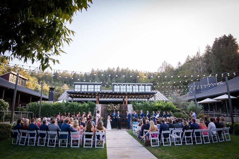 Outdoor ceremony with a barrel altar and dangling lights at Brasswood Estate in Napa, CA   PartySlate