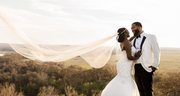 Bride and groom with bride's veil blowing in wind against landscape backdrop   PartySlate