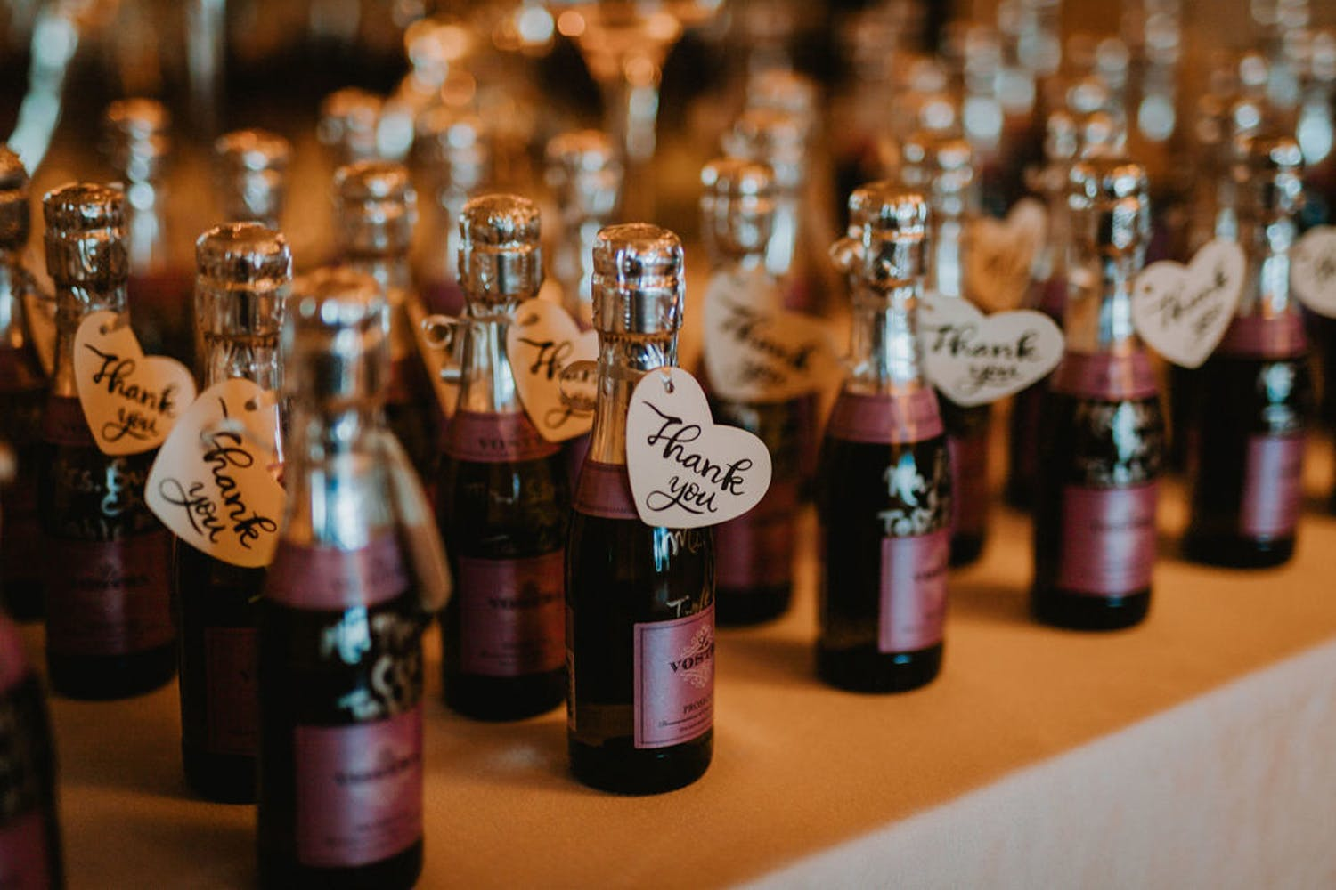 Mini Champagne bottles with purple labels for wedding anniversary party | PartySlate