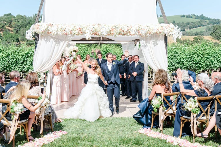 Newlyweds rejoice at the altar as loved ones cheer and photograph at beautiful outdoor wedding at deLorimier Winery in Geyserville, CA   PartySlate