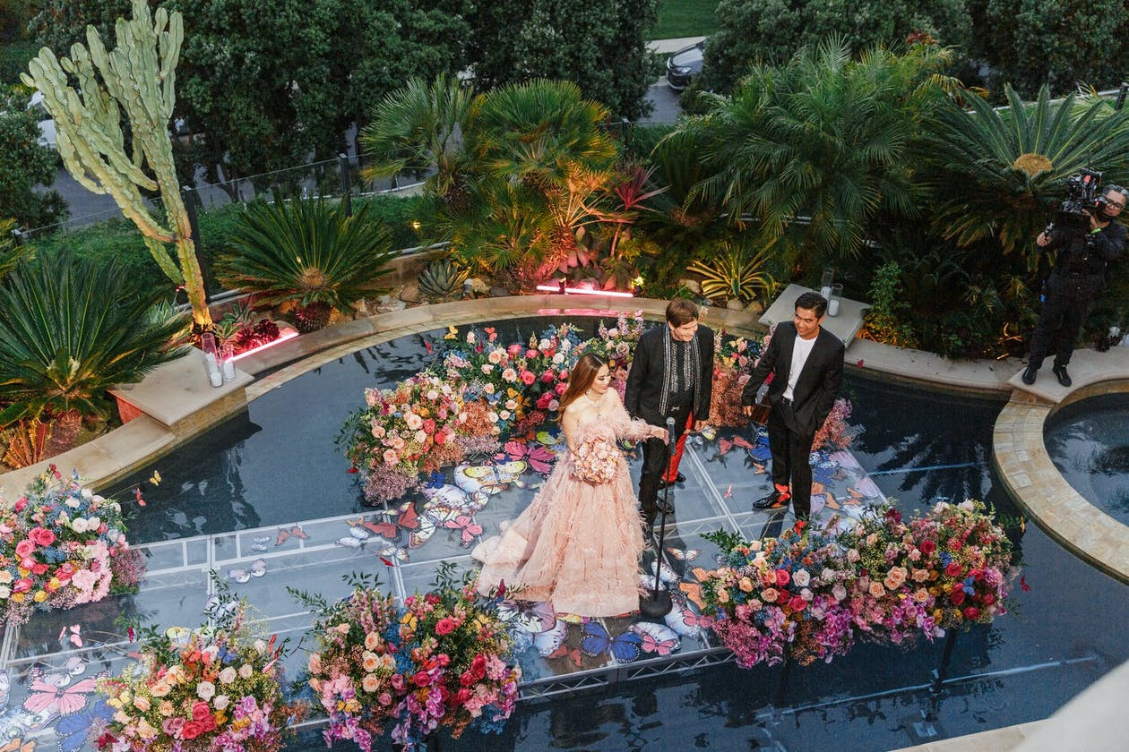 Anniversary Party Ideas: Couple renews vows on floating wedding aisle lined with bright and colorful flowers | PartySlate