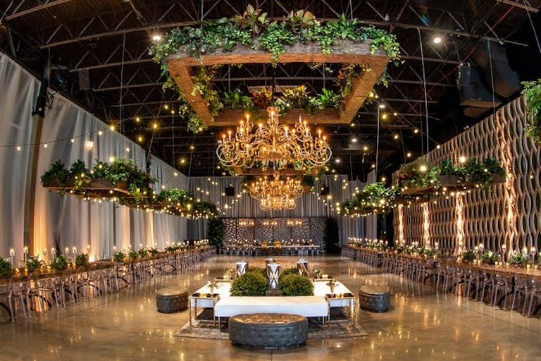 industrial wedding venue with white drapery, greenery, and chandeliers at Geraghty in Chicago   PartySlate