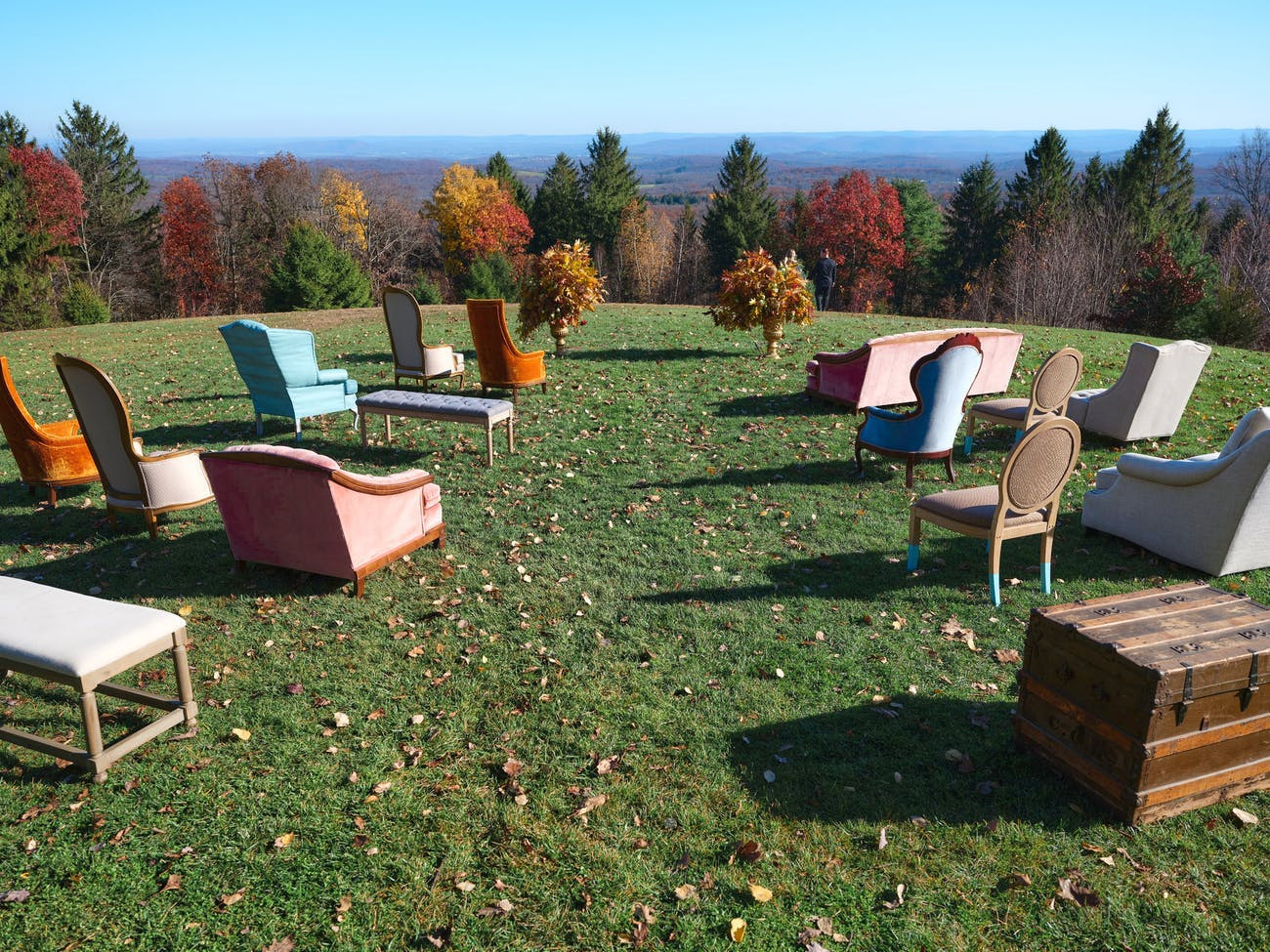Outdoor autumn wedding ceremony with eclectic and colorful individual sofa seating and view of changing leaves   PartySlate