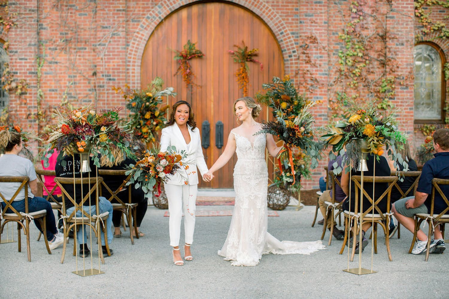 Two brides during recessional at boho-style vineyard micro wedding   Partyslate