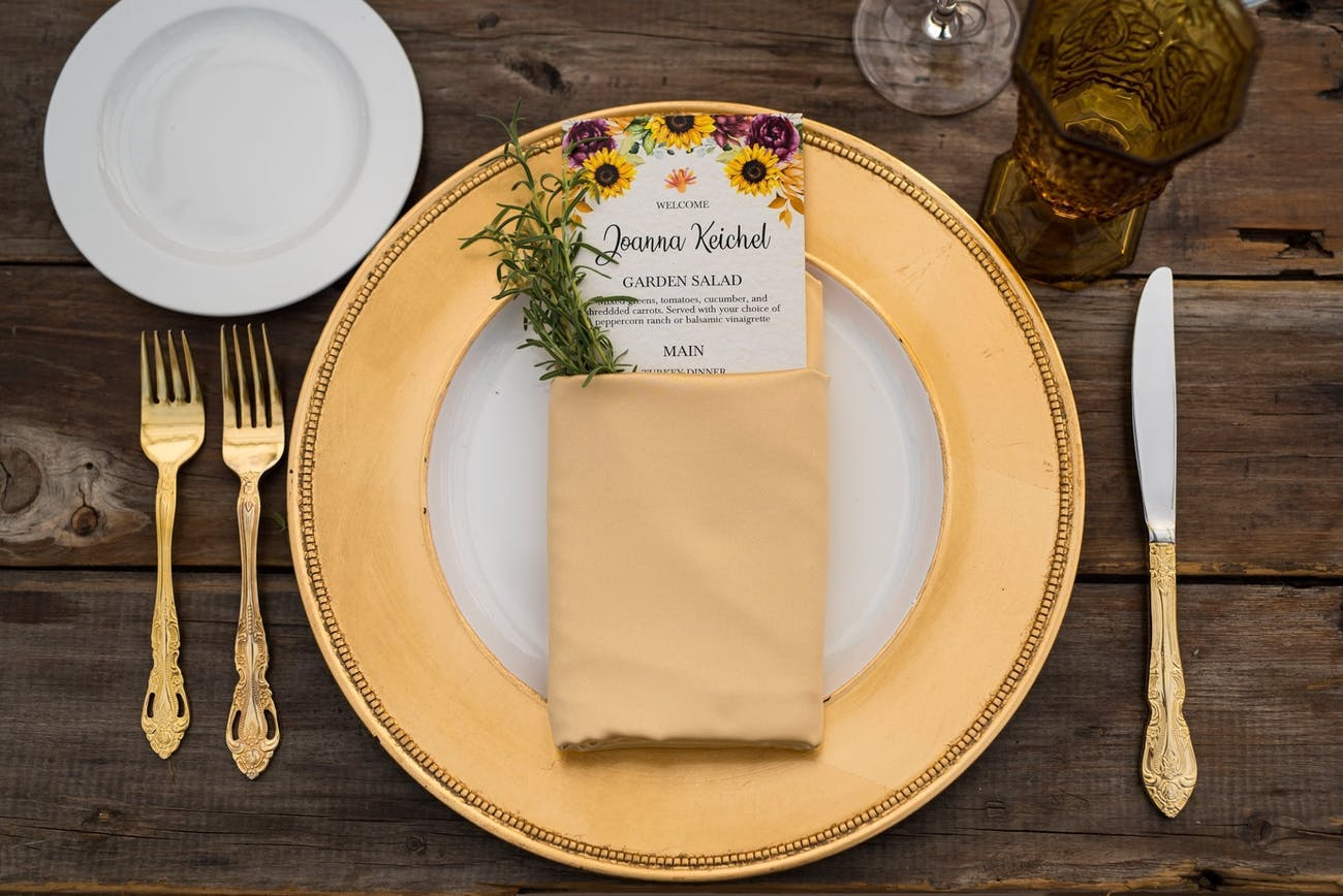 Gold wedding dinnerware with taupe napkin folded around menu with purple blooms and sunflower designs   PartySlate