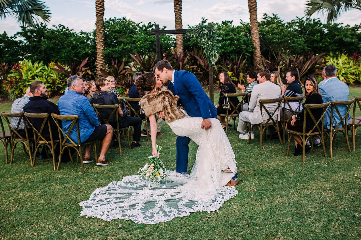 Bride and groom kiss during recessional of Tuscany-inspired micro wedding   PartySlate