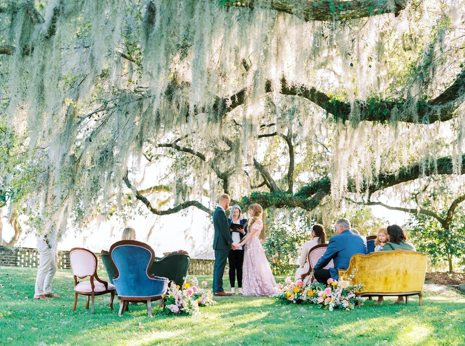 Elopement wedding ceremony in front of willow tree with colorful and eclectic vintage seating   PartySlate