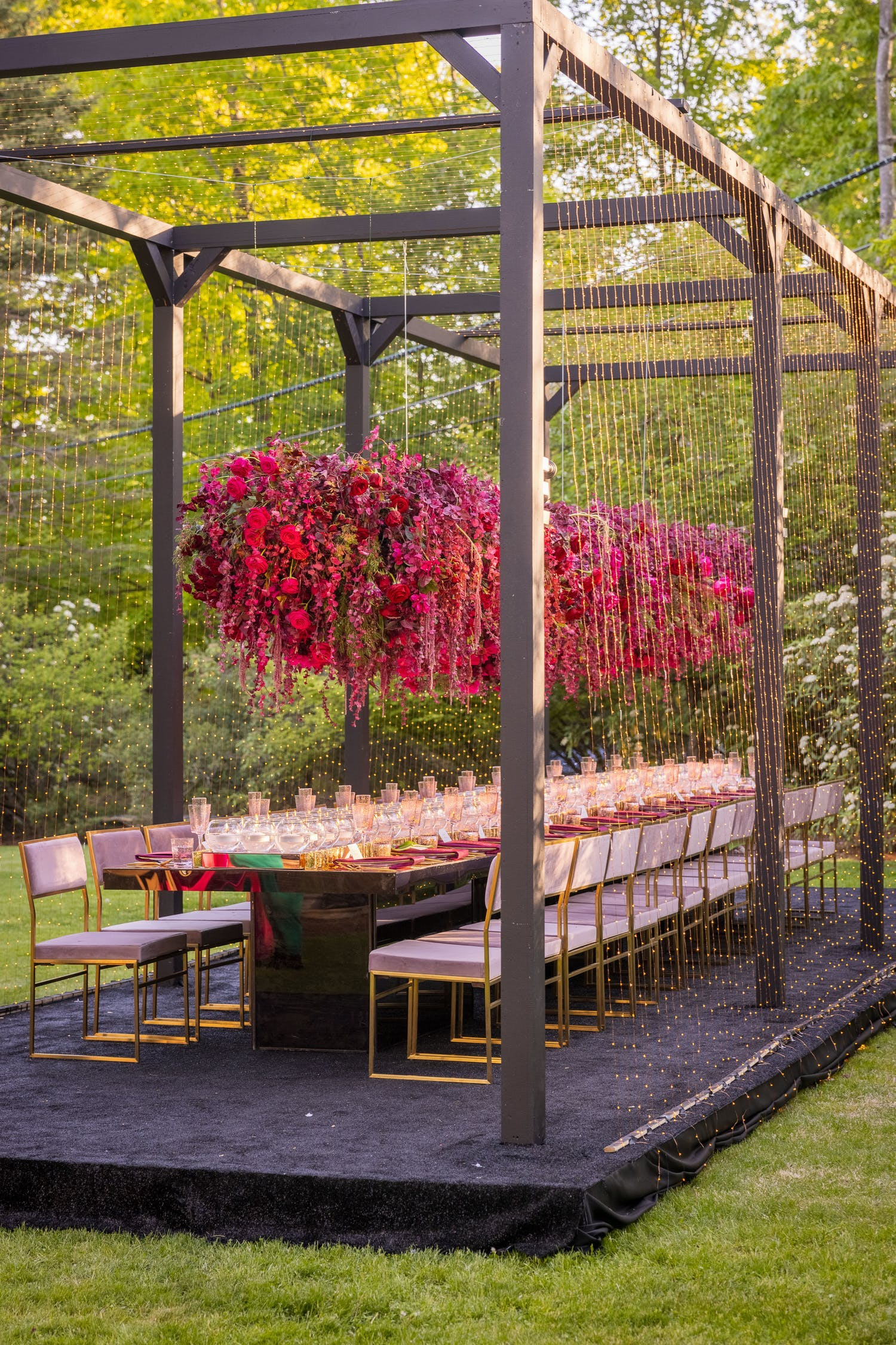 King's Table with Overhanging Pink Floral Centerpieces Suspended from Wooden Cabana with String Light Tassels   PartySlate