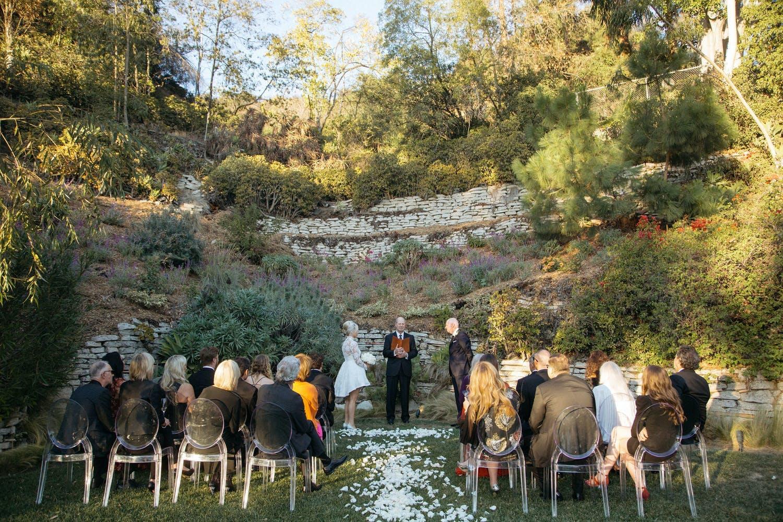 Elegant backyard wedding ceremony with white petal aisle   PartySlate