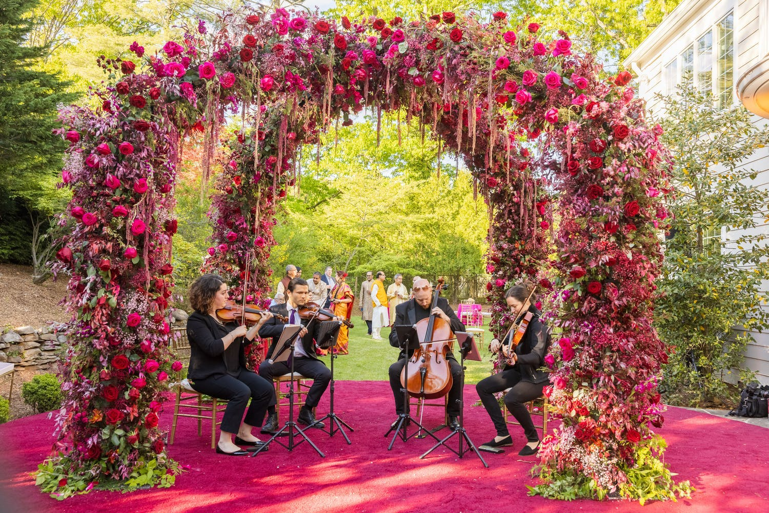 String quartet plays under double arch of bright pink blooms for wedding cocktail hour   PartySlate