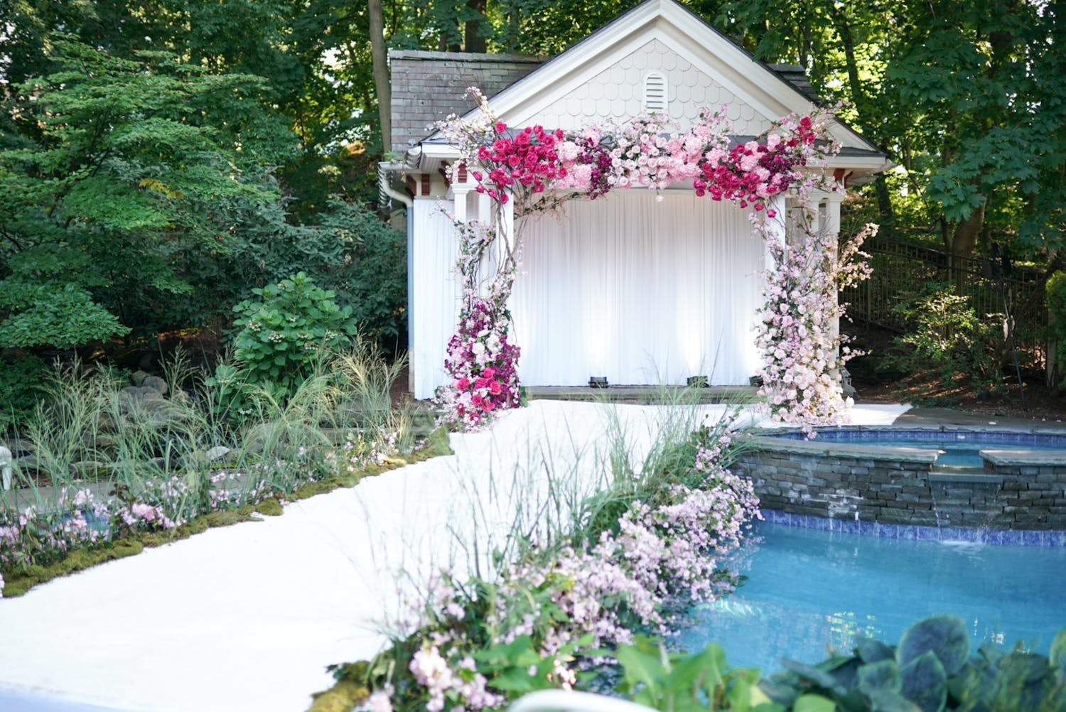 Backyard wedding with white aisle running alongside inground pool and pink floral arch against small white building   PartySlate