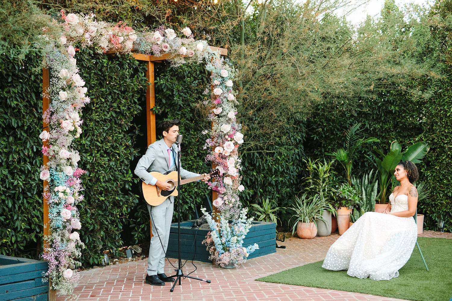 Beneath a whimsical floral arch, groom sings and play guitar for bride at micro wedding reception   PartySlate