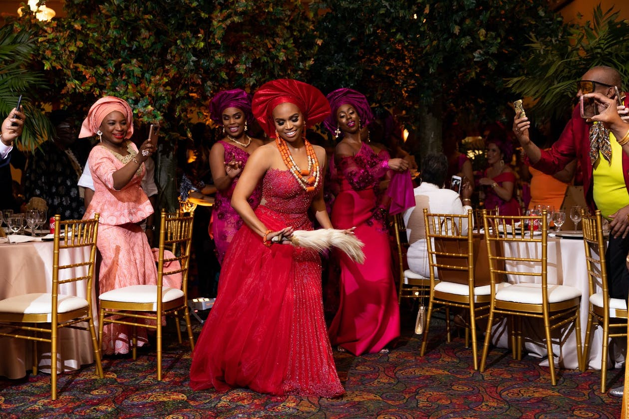 Bride dances in red dress and gele before her female relatives at a Nigerian wedding | PartySlate