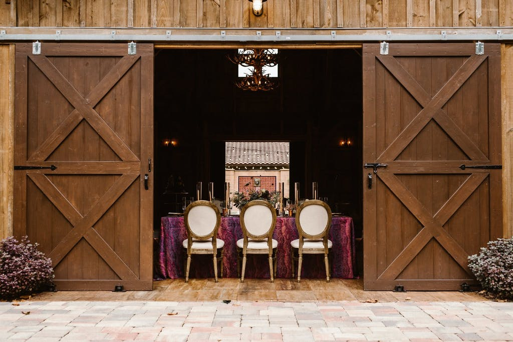 Intimate barn wedding with plum-colored linen and white seating   PartySlate