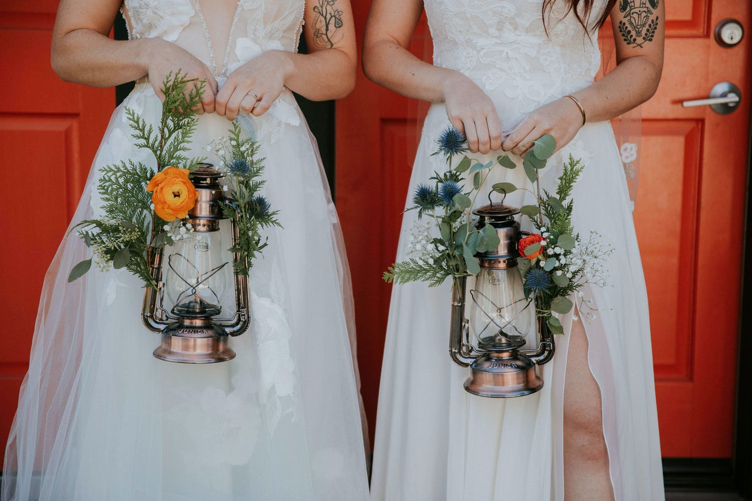 Two brides hold lanterns decorated with orange blooms and Oxford blues, one of PartySlate's favorite fall wedding ideas   PartySlate