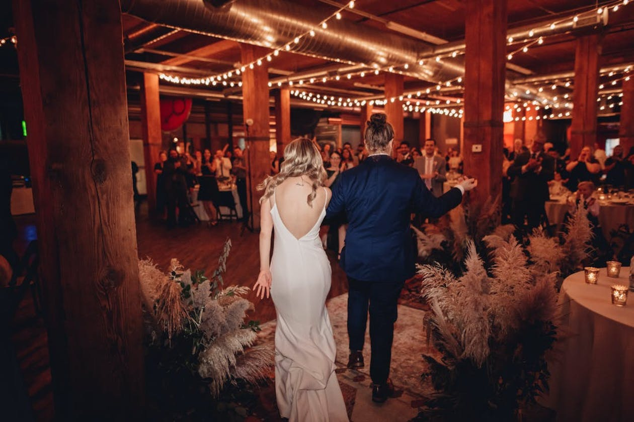 Couple walks into Lacuna Events by LM with overheard string lights   PartySlate