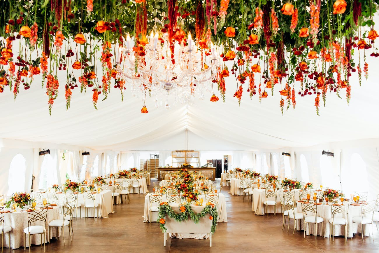 White tented wedding with upended orange blooms and greenery for ceiling décor   PartySlate