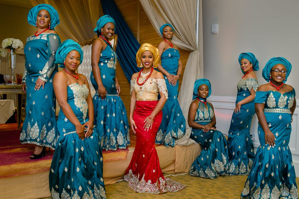 Bride in red and gold wedding attire poses with maidens in blue aso-ebi at Nigerian wedding | PartySlate