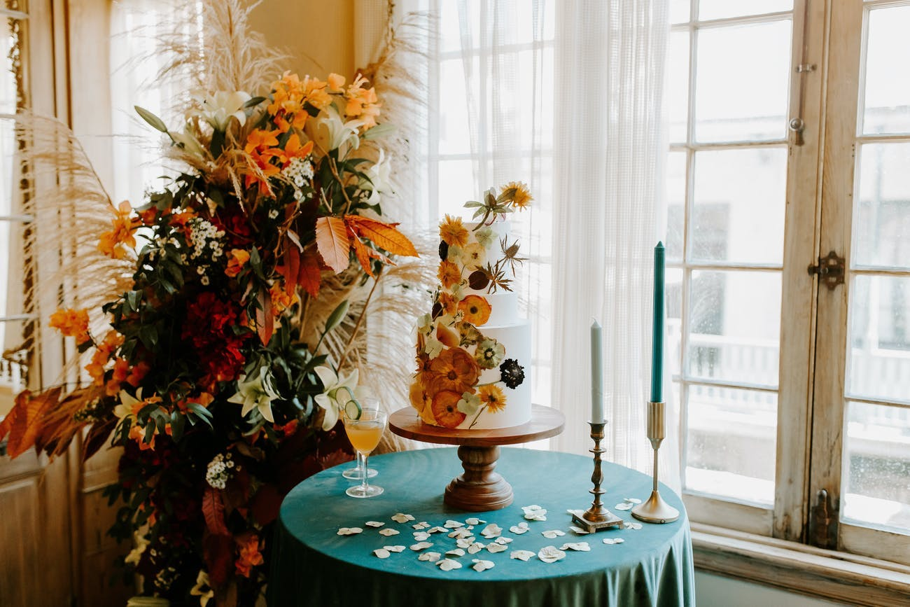White wedding cake with pressed autumn flowers and accompanying fall-hued floral décor   PartySlate