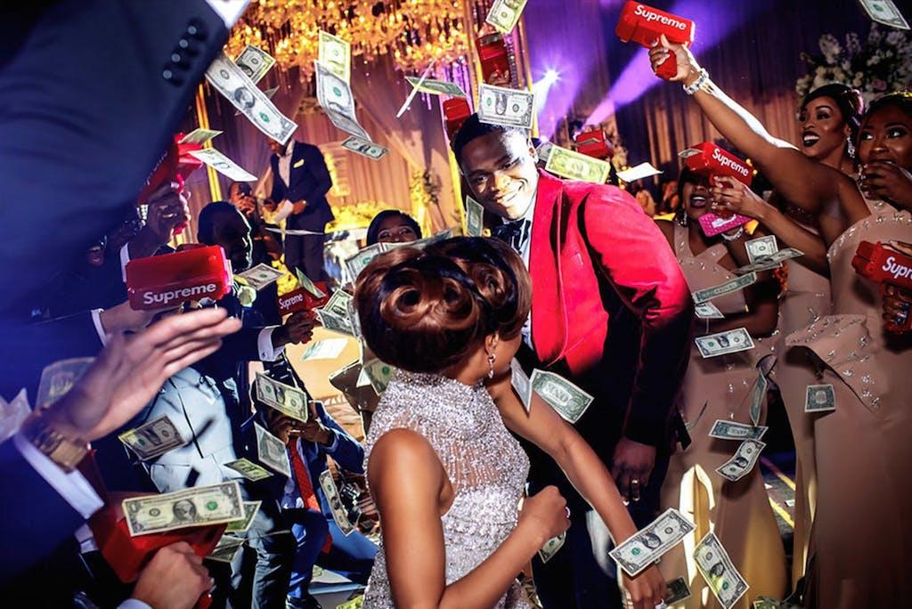 Money spray at vibrant Nigerian-American wedding at Royal Sonesta Houston | PartySlate