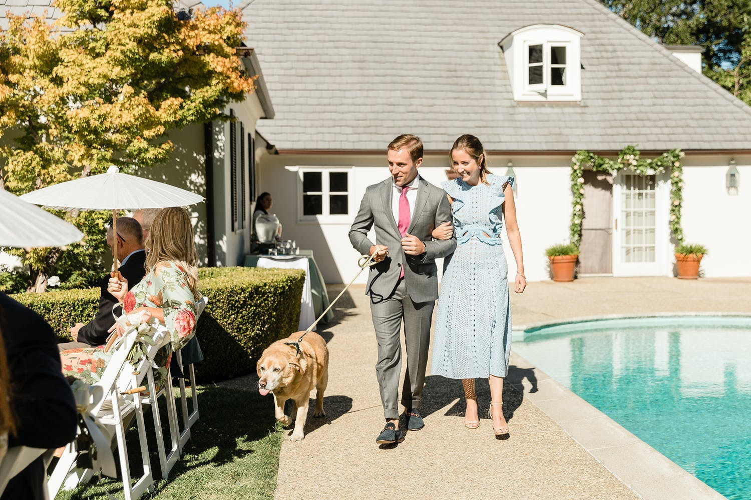 Bride, groom, and their pet dog walk down the aisle next to their backyard pool   PartySlate
