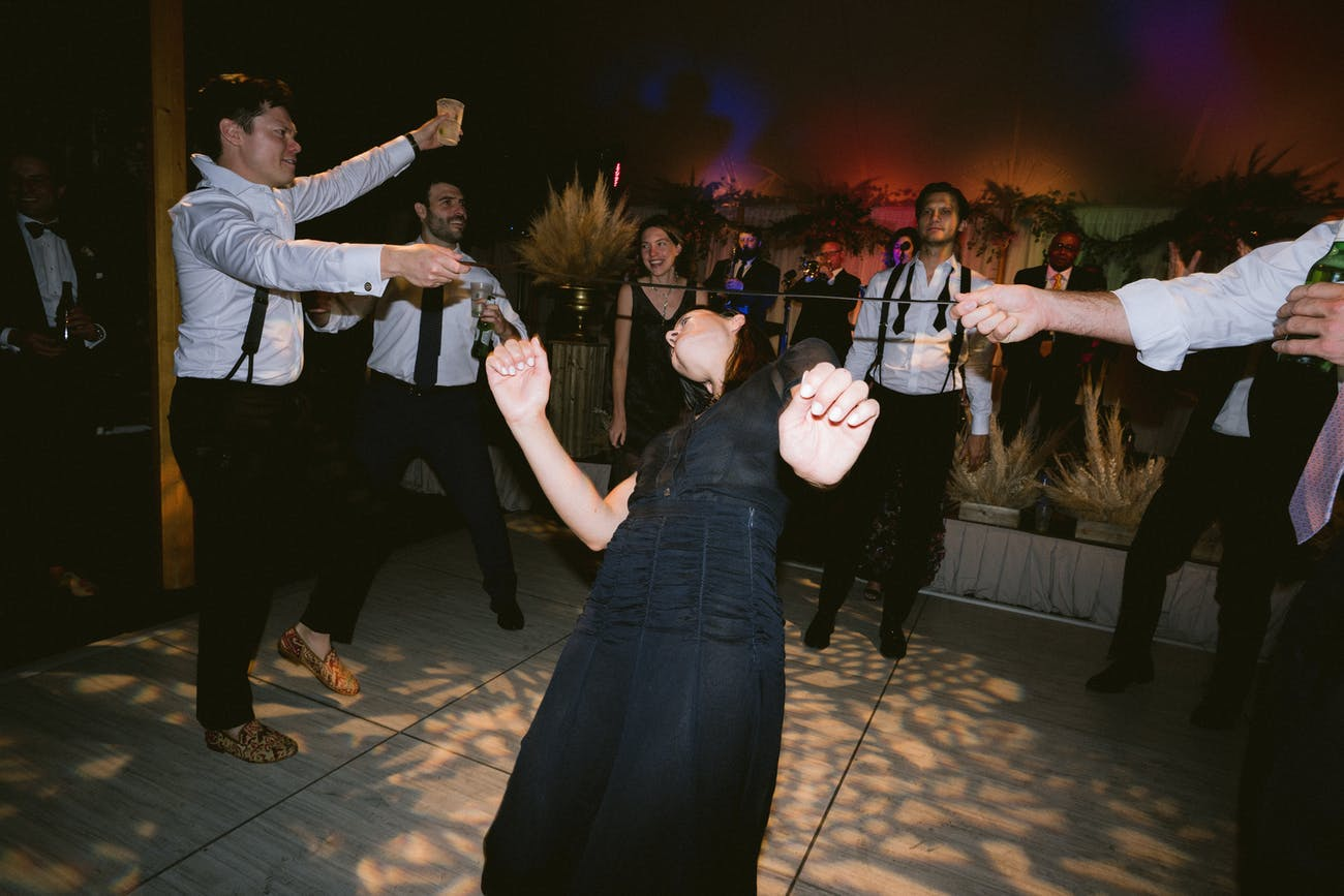 Woman dances limbo-style on dance floor with autumn leaf lighting projections   PartySlate