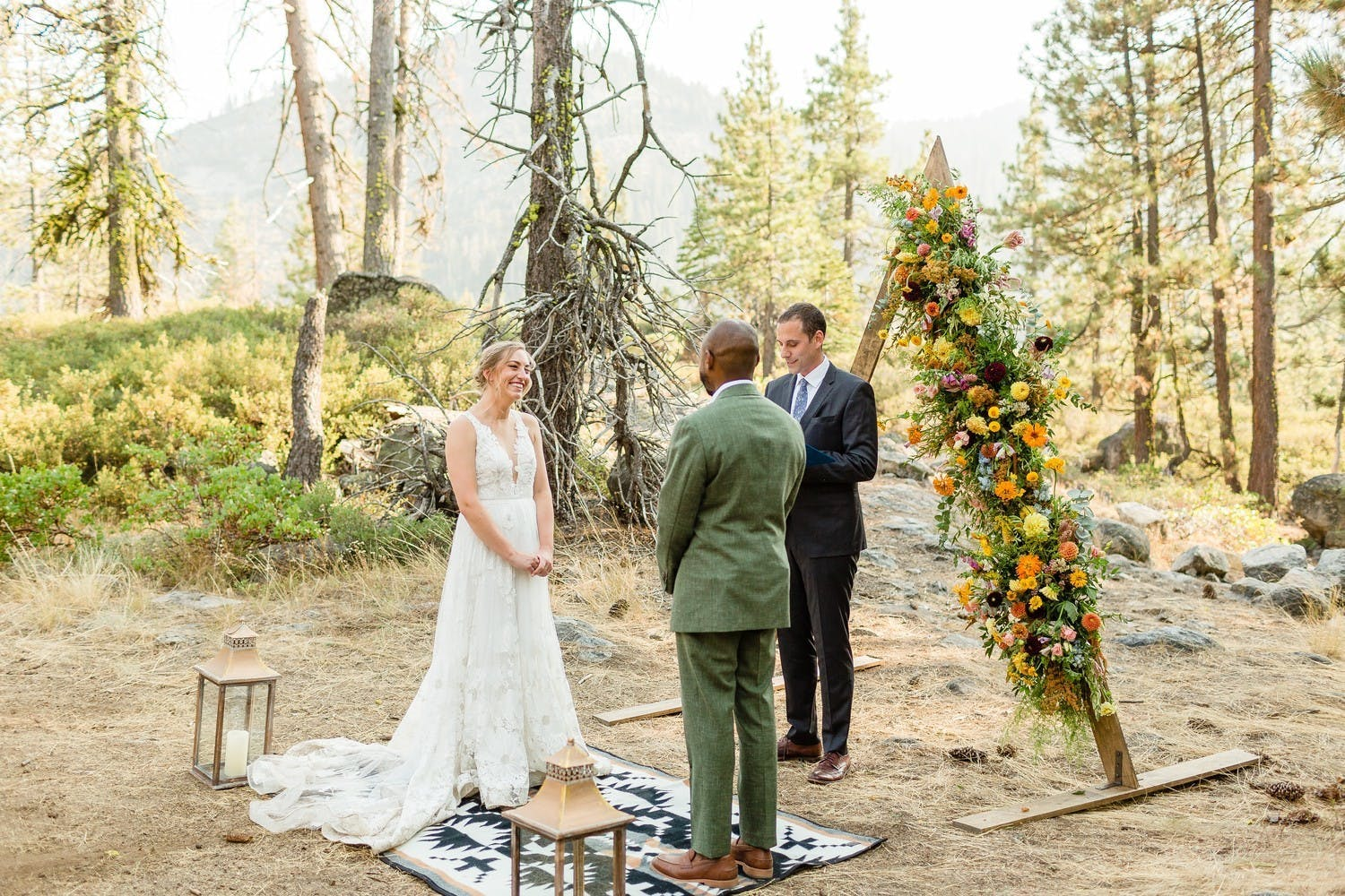 intimate micro wedding ceremony in woods with triangle arch with one side covered in flowers   PartySlate