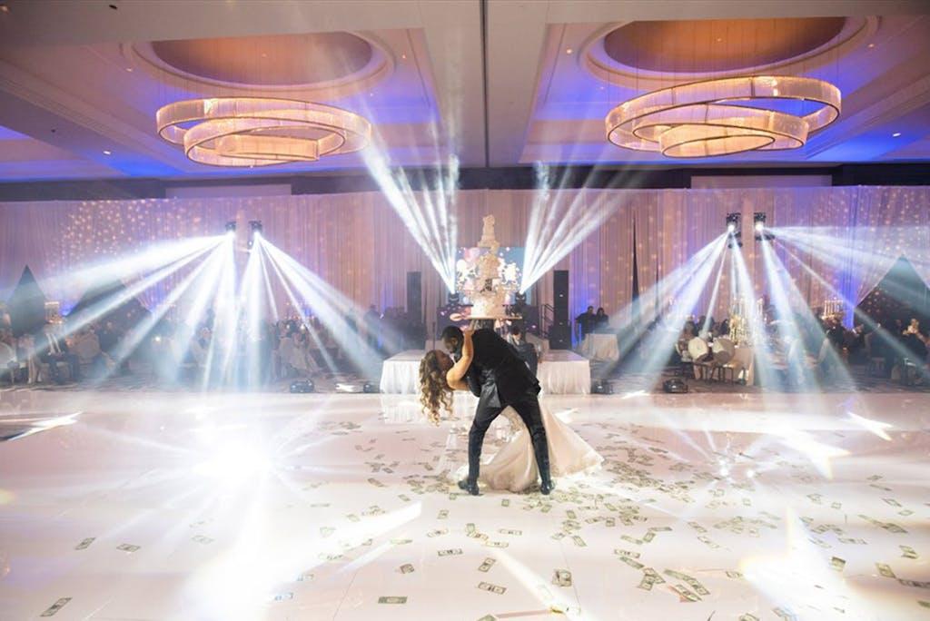 "Bride and groom wear western wedding attire on dance floor ""sprayed"" with money at formal Nigerian wedding reception | PartySlate"