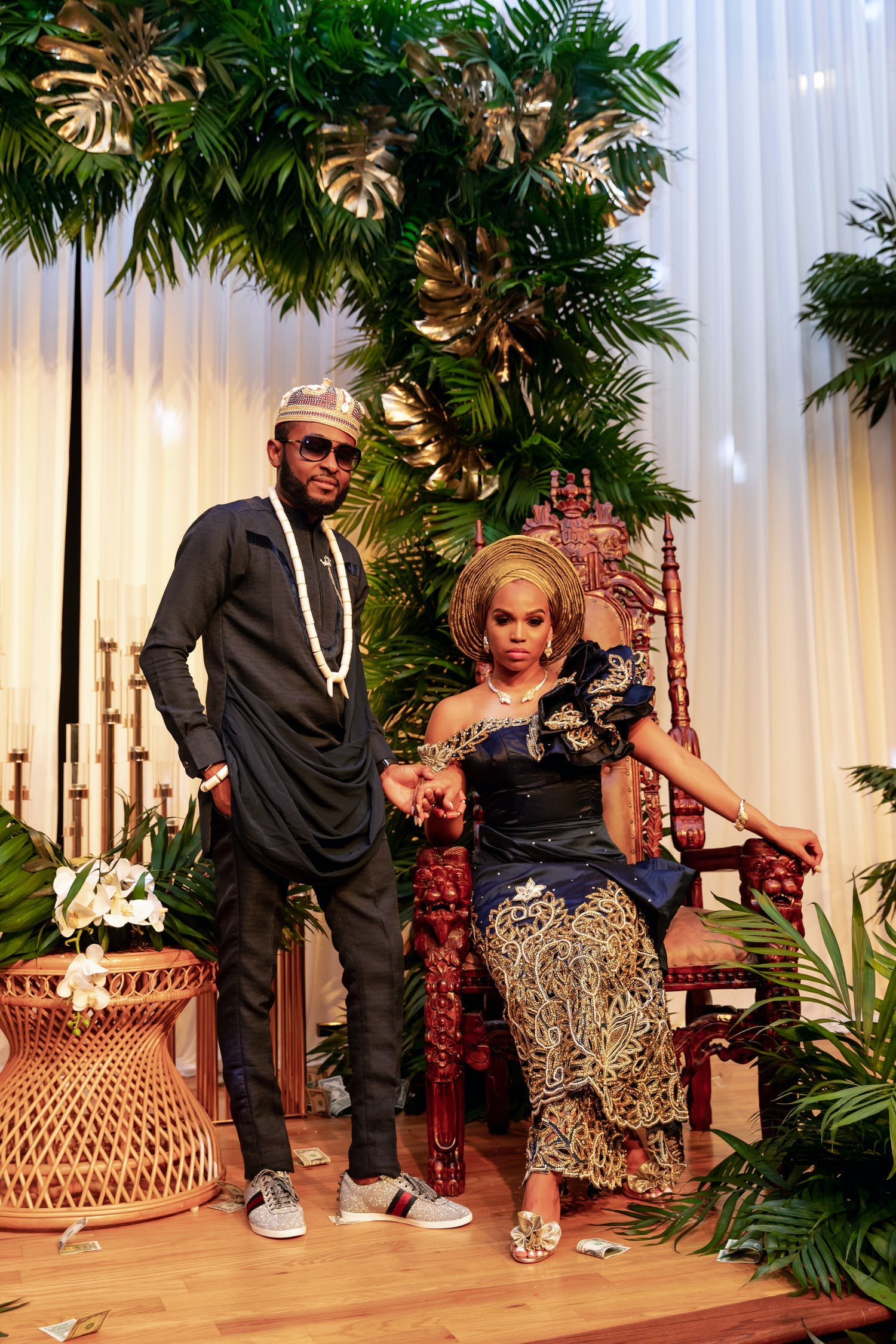 Bride and Groom pose in front of tropical foliage at Nigerian Wedding | PartySlate
