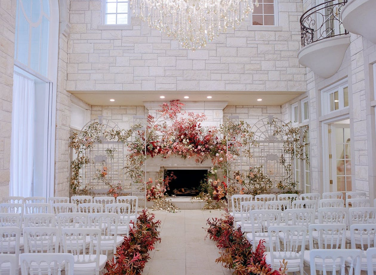 Indoor fall wedding with terracotta flower décor and white brick backdrop with fireplace   PartySlate