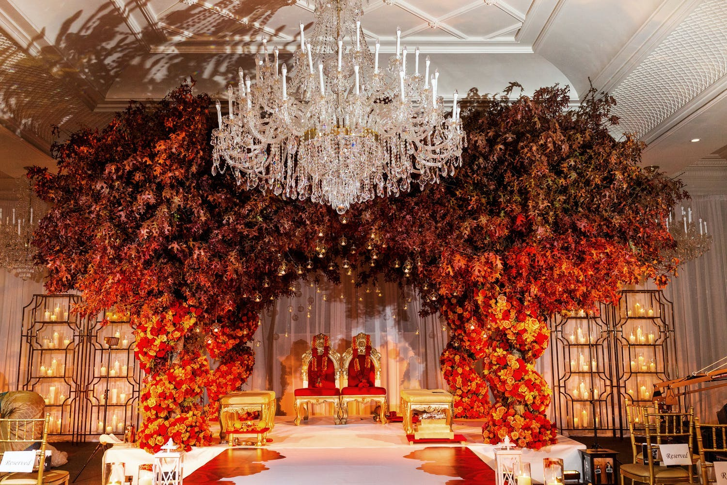 Fall wedding mandap with red and orange flower pillars and crown of autumn leaves   PartySlate