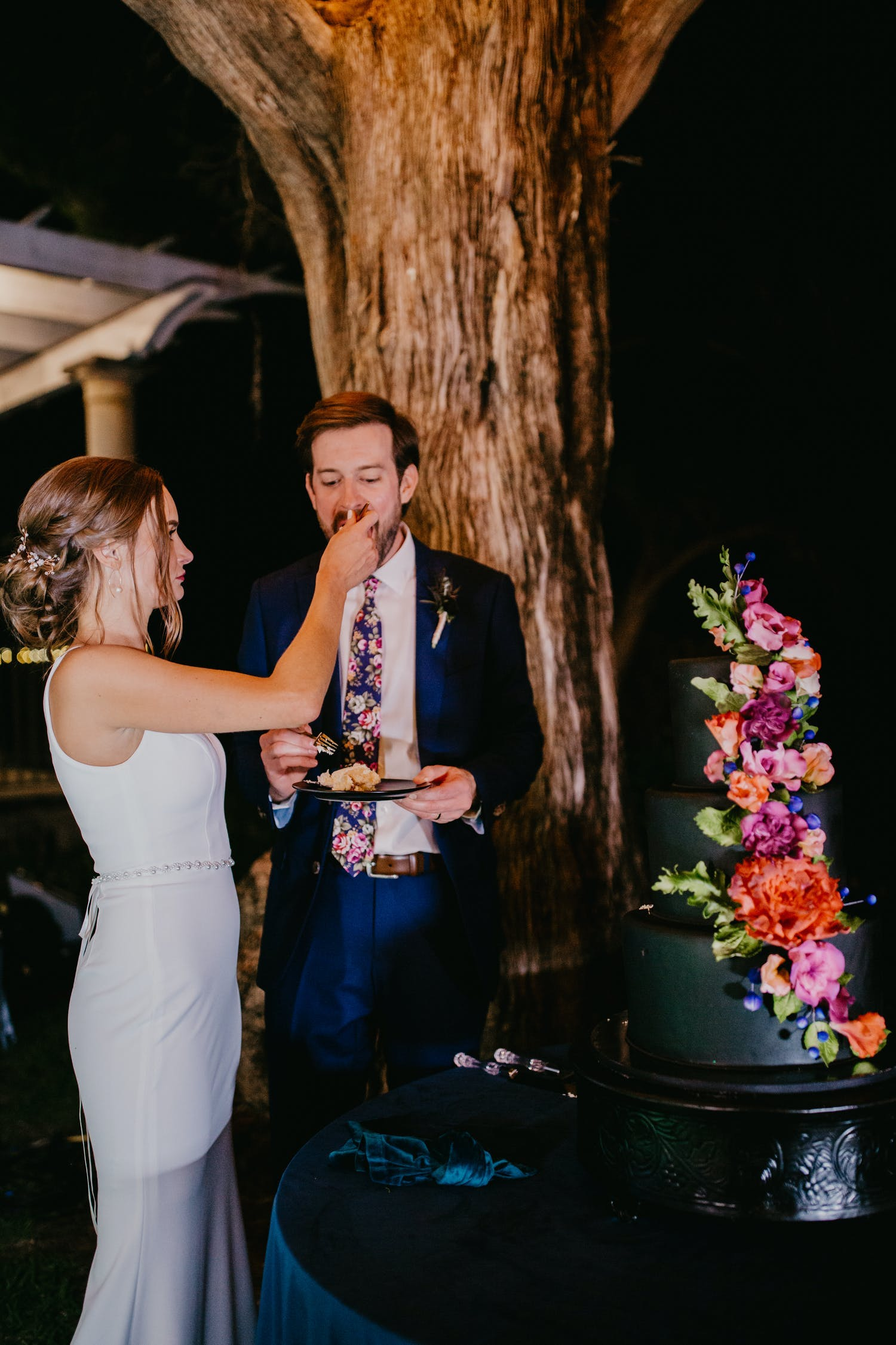 Bride and groom cut black wedding cake with colorful flowers at evening outdoor small wedding   PartySlate