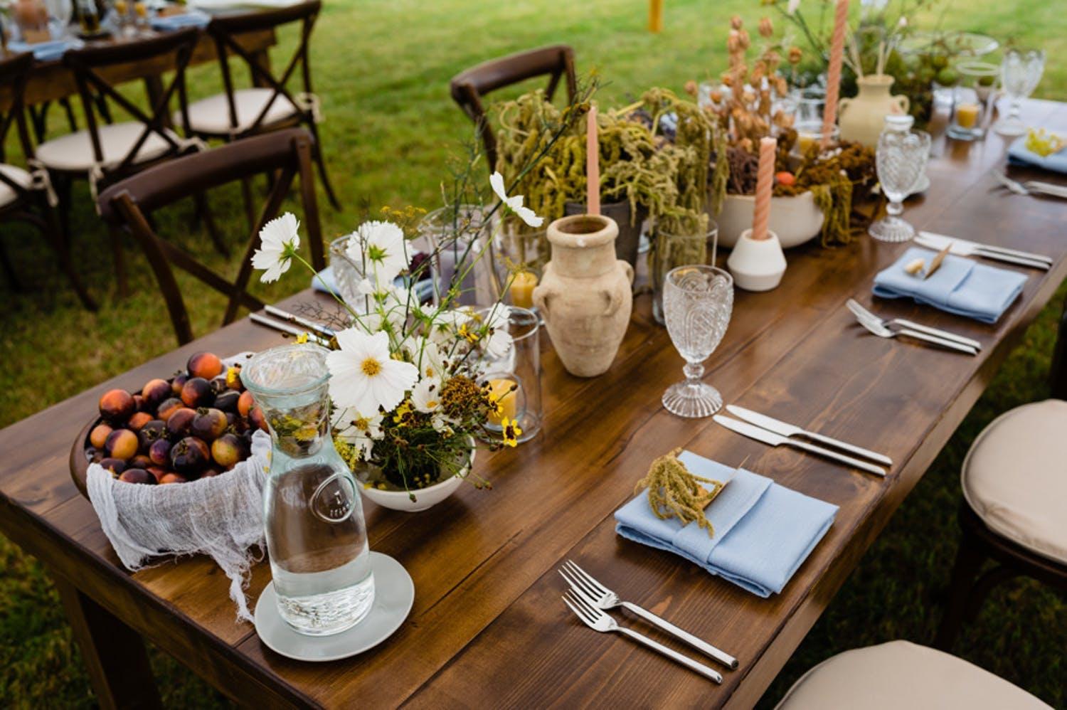 Walnut farm table filled with rustic pottery, green amaranth, and fall fruits for fall wedding   PartySlate