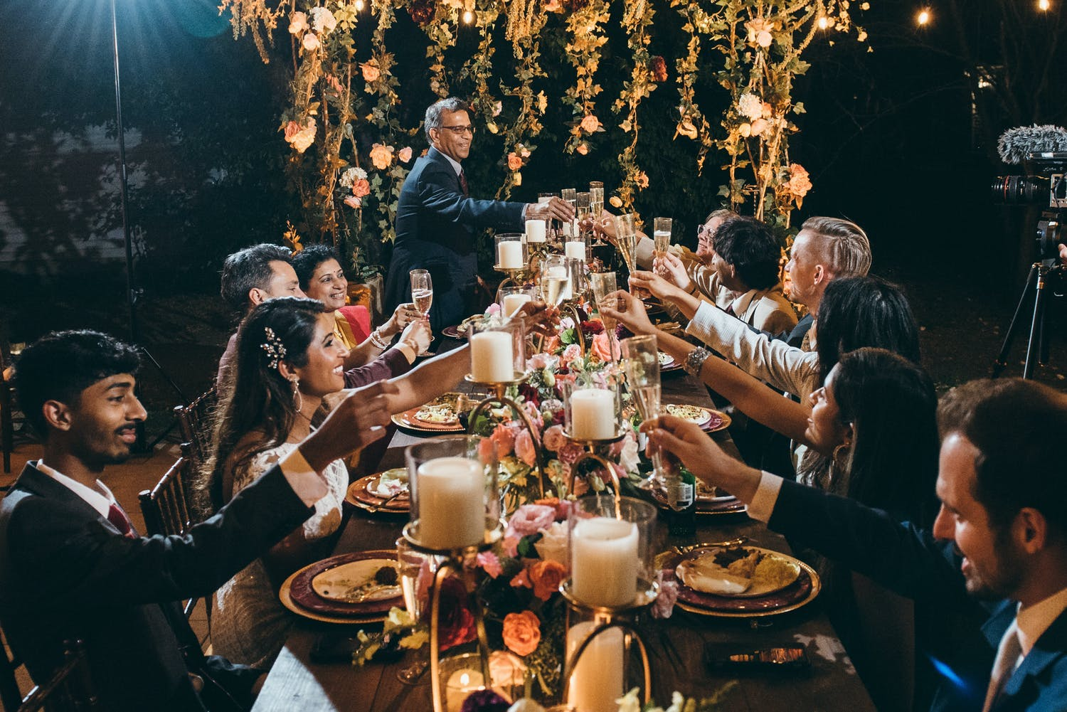 Night time wedding reception with king's table laden in candlelight and a floral installation at one end   PartySlate