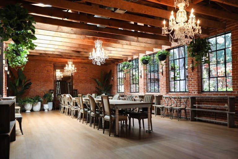 Salle at Carondelet House with exposed brick, greenery, and king's table for holiday party | Partyslate