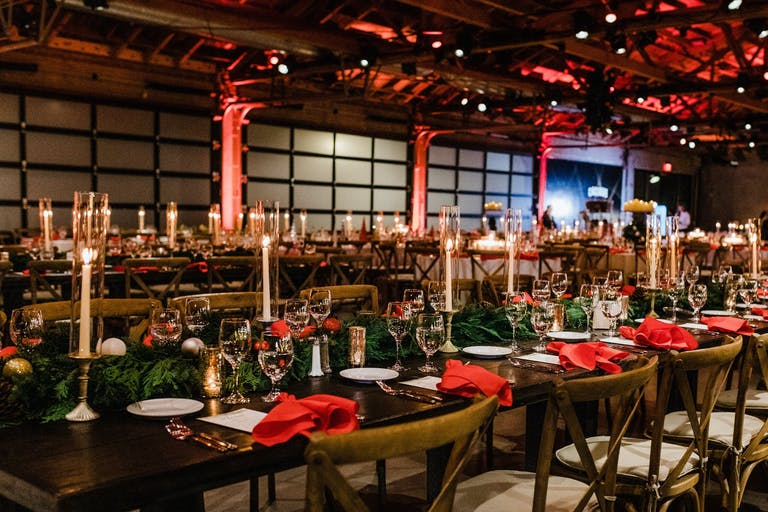 Holiday party at Studio 14 at City Market Social House with red uplighting and festive greenery | PartySlate