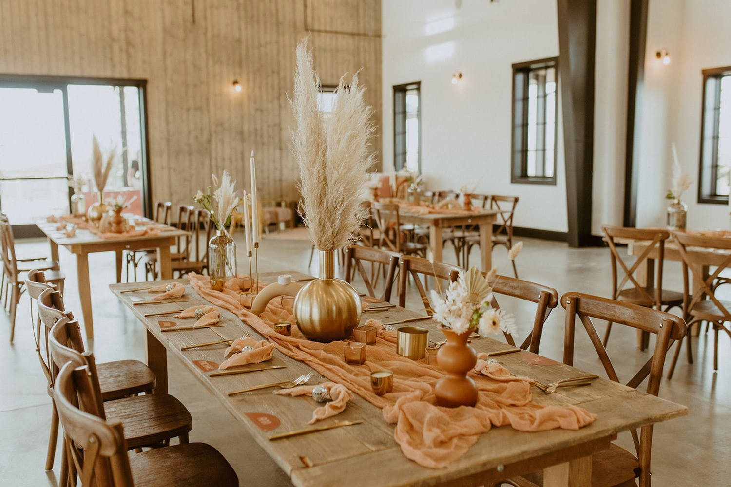 Modern fall wedding table with pottery-colored table runner and pampas grass in gold pumpkin vase   PartySlate
