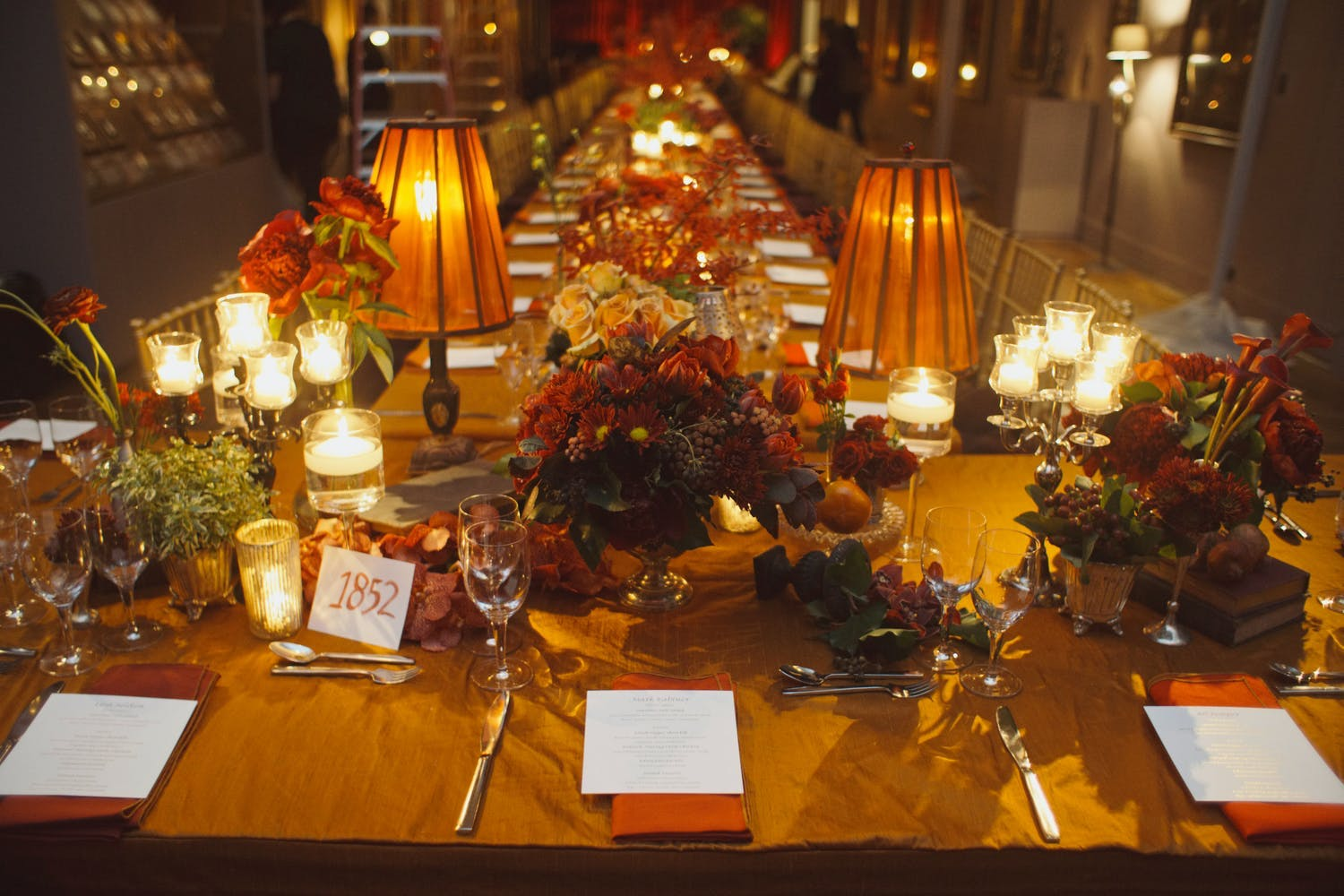 Fall wedding table with amber lamps, vintage books, and gold and flowers   PartySlate