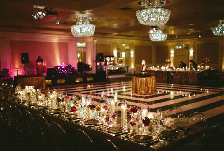 Starlight Ballroom at Fairmont Miramar Hotel & Bungalows with black and white dance floor, mirrored tabletops, pink florals, and candlelight | PartySlate