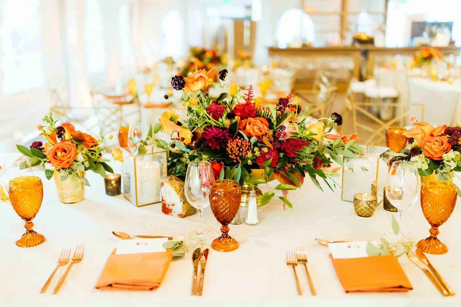 Fall-hued wedding floral centerpiece with amber glassware and copper-hued napkins and cutlery   PartySlate