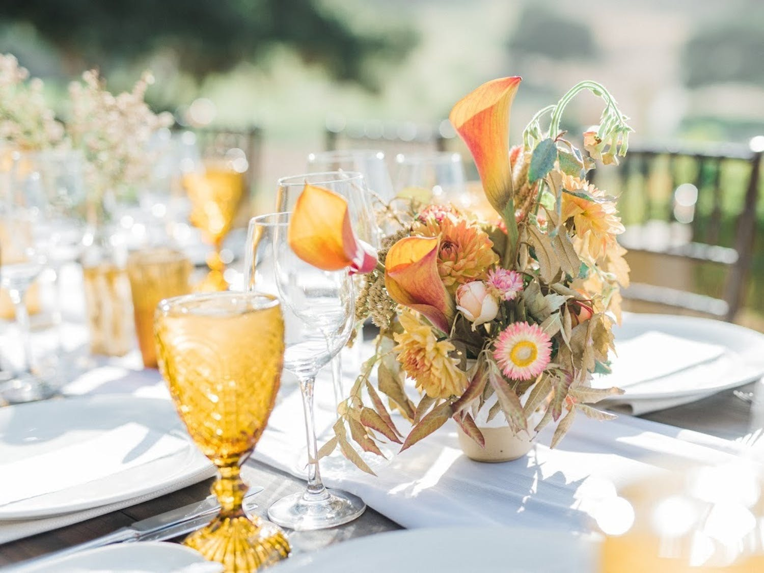 Wedding reception table with gold glassware and gold-hued fall floral centerpiece with organic fading leaves   PartySlate