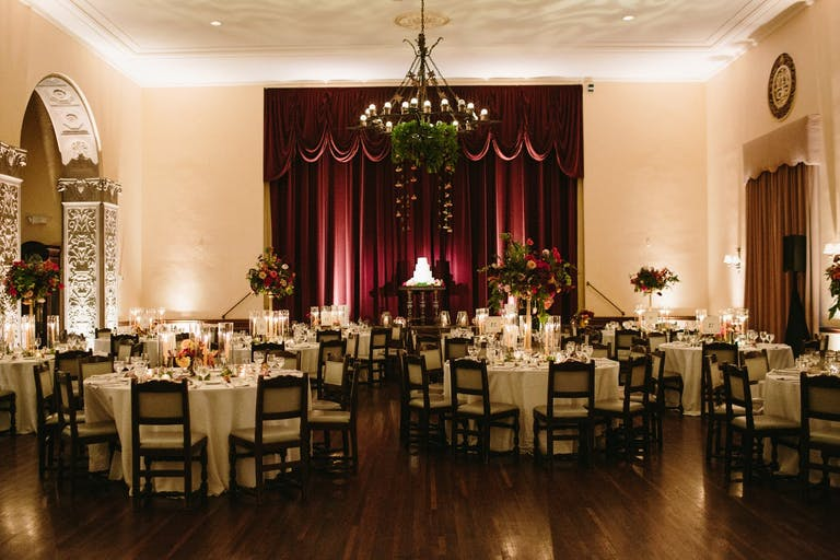 Full First Floor at The Ebell of Los Angeles with burgundy drapery and greenery on rustic chandelier | PartySlate